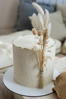 Изумительный минималистичный торт кремового цвета бежевого цвета, декорированный сухой колосом из пшеничного хлопка в стиле бохо-сканди