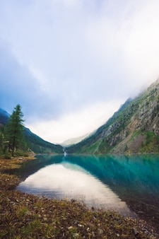 どんよりした天気の素晴らしい山の湖。山々、曇り空、朝日が澄んだ水に反射しました。