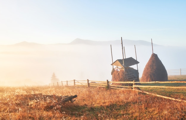 Amazing mountain landscape with fog and a haystack in autumn.
