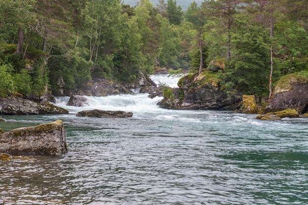 Изумительная горная река в норвегии. пейзаж. бирюзовая река. быстрый поток горной реки в норвегии