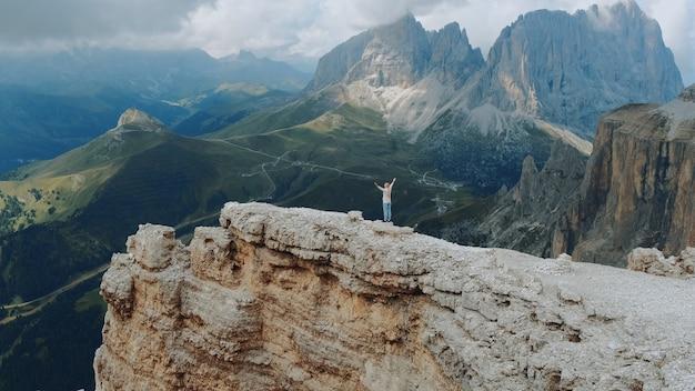 Удивительный вид на горы с женщиной, стоящей на вершине с протянутыми руками. ощущение свободы и наслаждение природой.