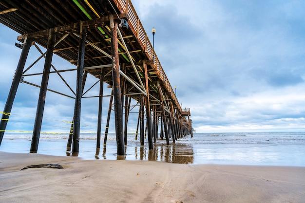 Удивительный природный ландшафт с рыболовным пирсом на берегу океана расположен в калифорнии в пасмурный день ocea