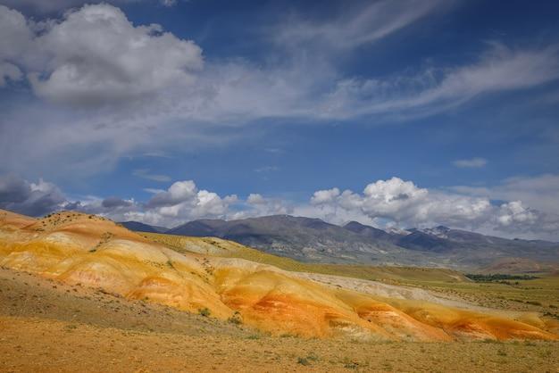 驚くべき自然現象-アルタイ山脈の火星の風景。白い雲と青い空を背景に色とりどりの岩。