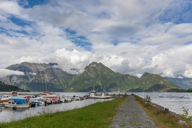 부두, 피요르드 및 산이있는 놀라운 자연 경관. 보기 앞의 보트 부두. 스칸디나비아 산맥, 노르웨이. 예술적인 그림. 뷰티 월드