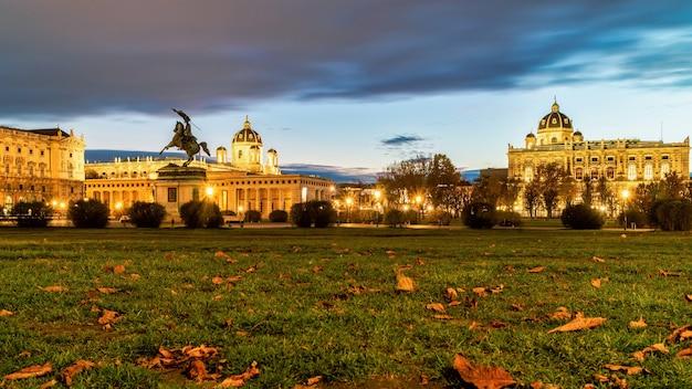 가을날 일몰의 흐린 하늘을 배경으로 오스트리아 비엔나의 영웅 광장인 헬덴플라츠(heldenplatz)가 보이는 놀라운 밤 풍경.