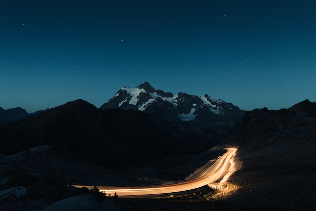Amazing night sky with a snowy rocky mountains in the middle and a dimly lit road