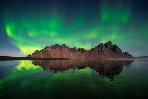 Amazing northern lights, aurora borealis dancing at vesturhorn mountain  in iceland
