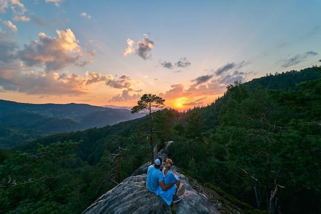 山の雲の後ろからの素晴らしいオレンジ色の日の出。山の頂上に観光客のカップル。山の中の松林。山の風景。旅行、休暇、観光。