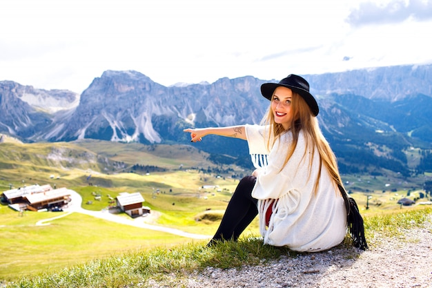 Amazing outdoor portrait of boho stylish woman posing at luxury resort with breathtaking mountains view, showing by her hand to italian dolomites.