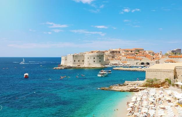 Удивительный панорамный вид на старый порт дубровника со средневековыми укреплениями на адриатическом море и пляж банье, хорватия, европа.