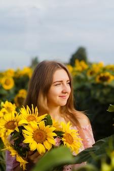 Amazing photo, beautiful young blonde woman standing among sunflowers