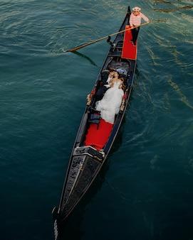 ヴェネツィアの運河に乗る際のゴンドラでのカップルの素晴らしい写真撮影