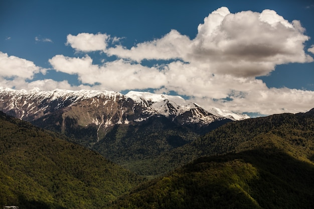 Удивительная картина зеленого горного пейзажа с голубым небом и белыми облаками