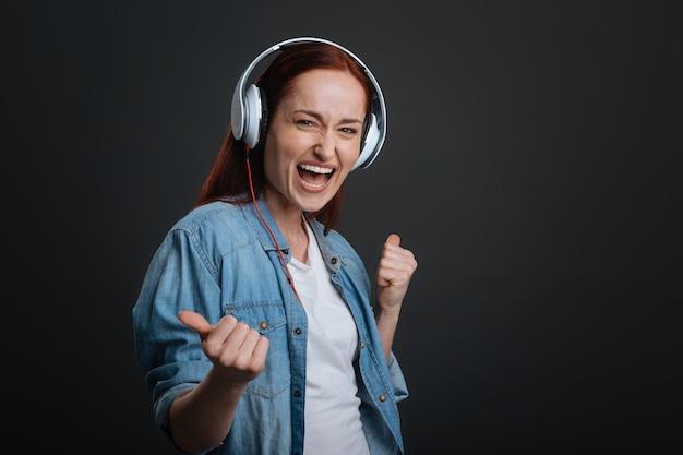 Потрясающий плейлист. симпатичная великолепная восторженная женщина тестирует свои новые наушники, играя свои песни, стоя изолированно на сером фоне