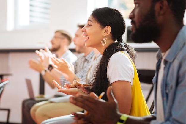 놀랄 만한. 성공적인 연사를 듣고 앉아있는 동안 웃고 박수를 보내는 긍정적 인 정서적 학생들