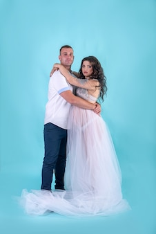 赤ちゃんを待っている、深い青色の背景に対してスタジオでポーズをとって素晴らしい妊娠中のカップル