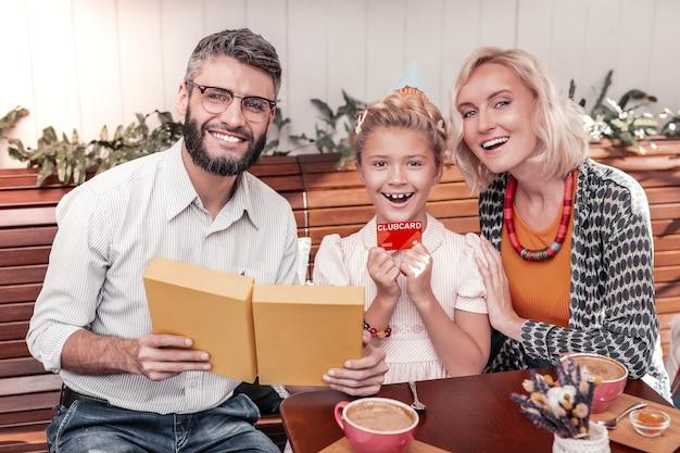 Прекрасный подарок. радостная возбужденная девушка улыбается вам, держа в руке свою клубную карту