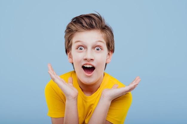 파란색 벽, 복사 공간에 고립 된 노란색 티셔츠에 놀라운 초반 이었죠 소년