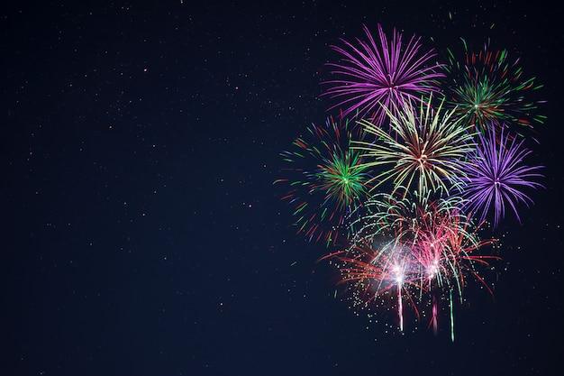 夜空の右側にある素晴らしい紫ライラック赤緑のお祝い花火、コピースペース。独立記念日、7月4日、年末年始は背景に敬礼します。