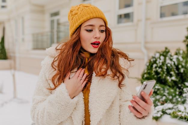 通りに立っている電話を持つ驚くべき赤毛の女性。スマートフォンを保持しているコートと帽子のかわいい生姜の女性。