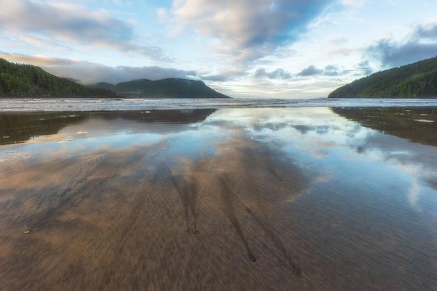 Удивительное отражение на пляже залива сан-джозеф в провинциальном парке кейп-скотт на острове ванкувер, британская колумбия, канада.