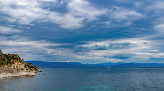 맑은 물과 코르푸 섬의 오래된 그리스 건축물이있는 놀라운 바위 섬