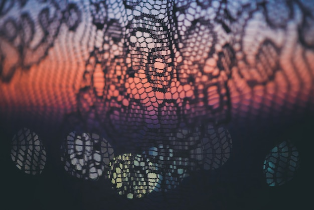 Amazing romantic sunset in window behind silhouettes of tulle texture.