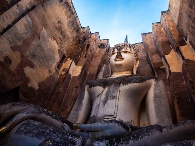 Удивительная сцена древней большой статуи будды внутри старой церкви с голубым небом в храме ват шри чум, в историческом парке сукхотай, объект всемирного наследия юнеско в таиланде, вид снизу.