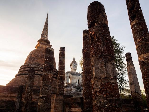 タイのユネスコ世界遺産であるスコータイ歴史公園の境内にあるワットマハタート寺院での大きな仏像と古い古代遺跡の素晴らしいシーン。