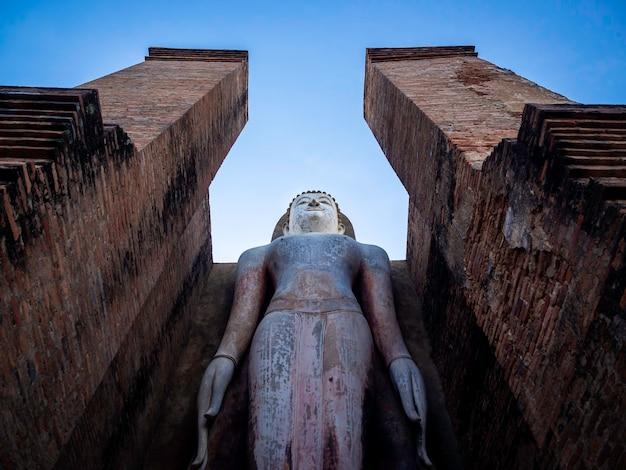 タイのユネスコ世界遺産であるスコータイ歴史公園の境内にあるワットマハタート寺院の大きな仏像と古い古代の建造物の素晴らしいシーン。
