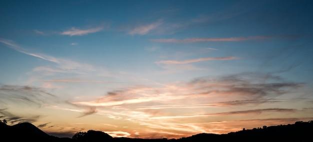 Удивительные пейзажи ярко-розового закатного неба над спокойным морем, омывающим холмистое побережье ранним вечером