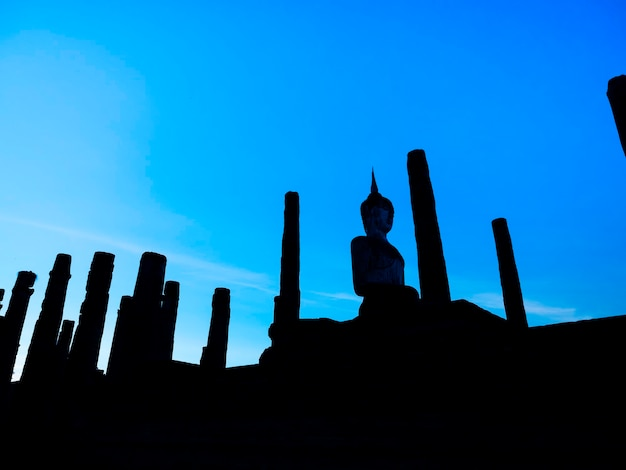 タイのユネスコ世界遺産である青空を背景に大きな仏像があるスコータイ歴史公園の境内にあるワットマハタート寺院のシルエットの素晴らしい風景。