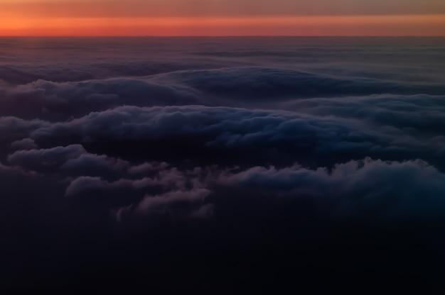 Amazing sea of dark fluffy clouds at sunset seen from airplane, orange horizon.
