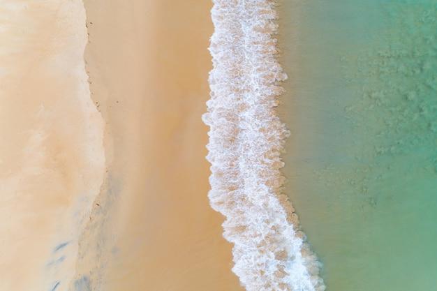 素晴らしい海の景色空撮砂浜と澄んだターコイズブルーの海の波がビーチに打ち寄せる