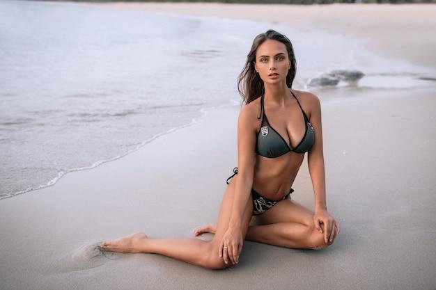Amazing sensual seductive woman sitting and resting on the beach, enjoying summer holidays