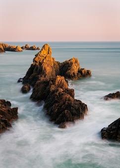 일몰 배경에 바위 해변의 놀라운 샷