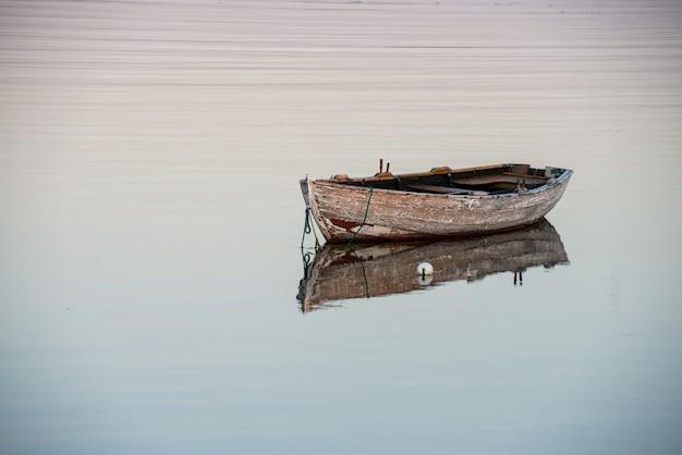 反射する湖の上の古い木製のボートの素晴らしいショット
