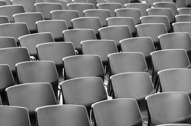 Удивительный снимок серых стульев, идеально расположенных в ряд