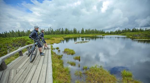 スロベニアのリブニカ湖の景色を楽しむ2人のサイクリストの素晴らしいショット