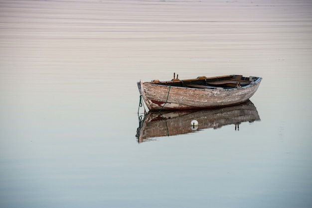 Amazing shot of an old wooden boat on a reflective lake