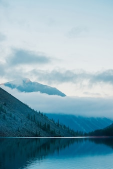 Amazing silhouettes of mountains and low clouds reflected on mountain lake