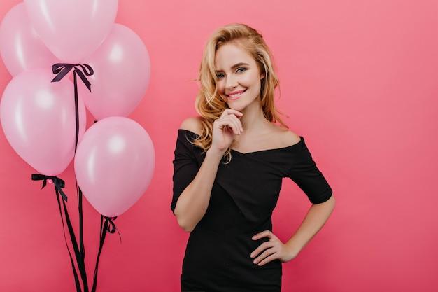 그녀의 생일에 기쁨과 함께 포즈를 취하는 놀라운 슬림 소녀. 핑크 인테리어로 서있는 황홀한 국방과 아가씨.