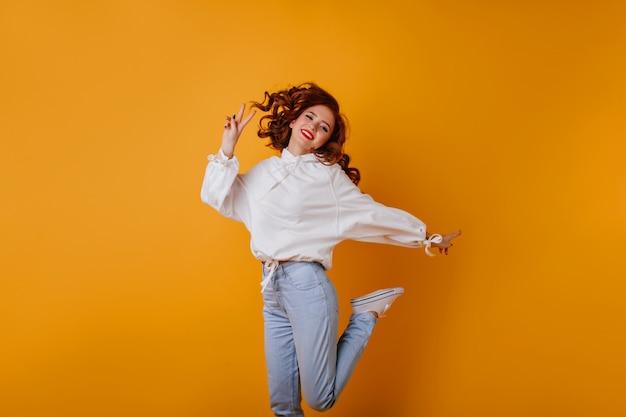Удивительно стройная дама дурачится. рыжая девушка в белой блузке прыгает и улыбается.