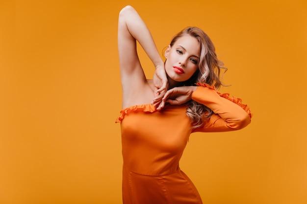 Incredibile donna sottile in abito arancione ballando in studio