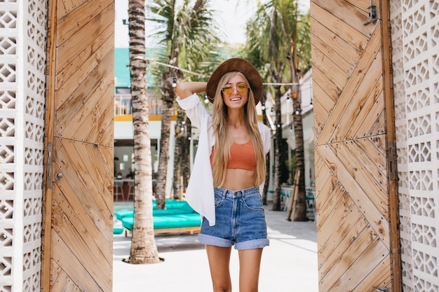 Amazing slim woman with beautiful smile enjoying summer at resort. portrait of graceful blonde female model in sunglasses spending time outdoor in hot morning.