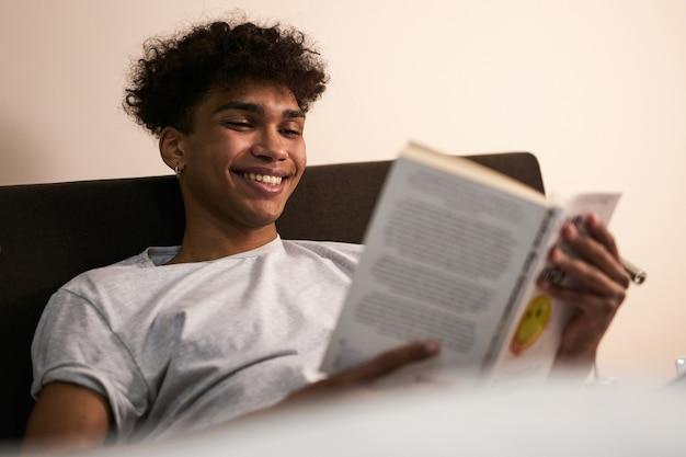 Удивительный рассказ портрет веселого брюнетки парня, лежащего в постели дома, улыбающегося во время чтения