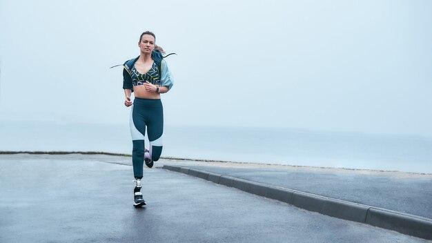 Удивительная сильная женщина-инвалид в спортивной одежде бежит на свежем воздухе у моря