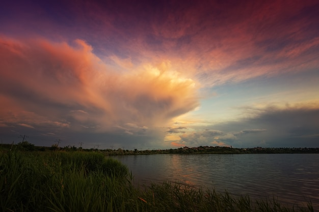 Amazing sunrise by the lake with colorful clouds and vegetation in the foreground