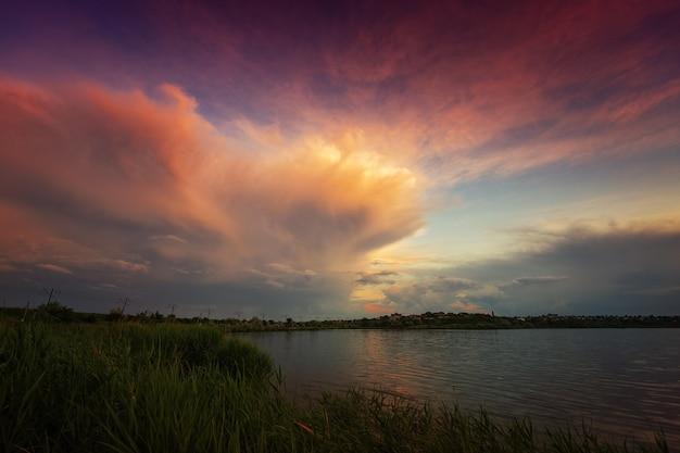 Удивительный восход солнца у озера с разноцветными облаками и растительностью на переднем плане.