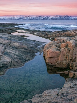 Amazing sunrise landscape with polar white snowy range of mountains. wonderful mountain landscape with a gorge and a cape on the shore of the barents sea.
